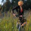 Young beautiful woman with bicycle resting in park on sunset — Stock Photo