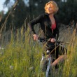 Young beautiful woman with bicycle resting in park on sunset — Stock Photo #32781567