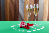 Two glases of champagne next to a heart shape candy — Stock Photo