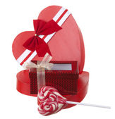 Red box in heart shape with a lollypop isolated on white backgro — Stock Photo