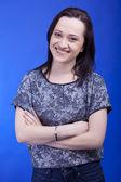 Sorridente bella ragazza caucasica con le mani incrociate sul retro blu — Foto Stock