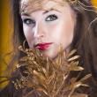 Portrait of beautiful gilr with a gold branch in hair — Stock Photo #25288421