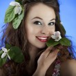 Girl with flowers in hair on blue background — Stock Photo #26298041