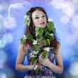 Stock Photo: Beautiful girl on abstract flower background with flowers in hai