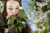 Gorgeous girl with flowers in hair on flower background. Profess — Stock Photo