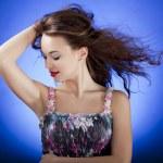 Sensual brunette model posing against a blue background — Stock Photo #27247251
