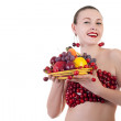 Smiling gorgeous woman with a plate of fruits isolated on white — Stock Photo