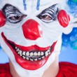 Scary clown person in clown mask on blue background — Stok fotoğraf