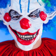 Scary clown person in clown mask on blue background — Stock Photo #29539799