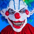 Scary clown person in clown mask on blue background — Stock Photo #29539803