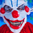 Scary clown person in clown mask on blue background — Stock Photo #29539805