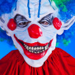 Scary clown person in clown mask on blue background — Stock Photo #29539807