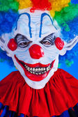 Scary clown person in clown mask on blue background — Stock Photo