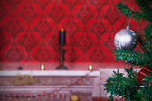 Christmas ball on a red vintage background with a burning candle — Stock Photo