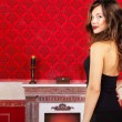 Glamour girl in evening dress on a red vintage background next t — Stock Photo #30369977