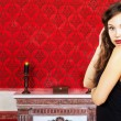 Gorgeous girl in black dress posing in a vintage room on a red b — Stockfoto