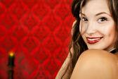 Lachende sensuele meisje op een rode vintage achtergrond met een brandend — Stockfoto