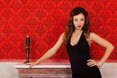 Sensuele vrouw in zwarte jurk op rode vintage achtergrond met een certificeringsinstantie — Stockfoto