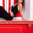 Sexy girl in evening dress on a sill in red vintage room fashion — Stock Photo