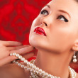 Beautiful womwith luxury pearls on red vintage background — Stok Fotoğraf #32379213