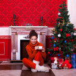 Beautiful girl inside a red vintage room with christmas decor — Stock Photo