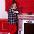 Girl in worm clothes inside a red vintage room with christmas de — Stock Photo