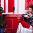 Girl in worm clothes inside a red vintage room with christmas de — Stock Photo #32782841