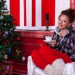 Girl in worm clothes inside a red vintage room with christmas de — Stock Photo #32782861