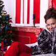 Girl in worm clothes inside a red vintage room with christmas de — 图库照片
