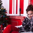 Girl in worm clothes inside a red vintage room with christmas de — Stock fotografie