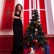 Gorgeous girl in evening dress in red vintage room with christma — Stock fotografie