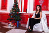Gorgeous girl in evening dress in red vintage room with christma — Stock Photo