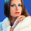 Beautiful woman in fur on blue background fashion glamour winter — Stock Photo