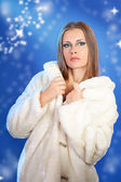 Sensual woman in a white fur on blue background winter fashion p — Stock Photo