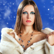 Sensual woman in white fur on blue winter background with snow — Stock Photo
