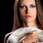 Beautiful woman in fur on black background — Stock Photo