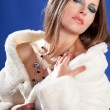 Beautiful woman in fur on blue background — Stock Photo