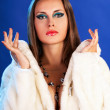 Sexy woman in fur on blue background winter fashion glamour styl — Stock Photo
