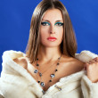 Sensual woman in white fur on blue background — Stock Photo #35642321
