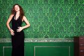 Beautiful brunette model in green vintage room posing — Stock Photo