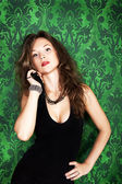 Gorgeous sexy girl on green vintage wall background — Stock Photo