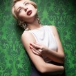 Sexy blonde on retro green wallpaper background — Stock Photo
