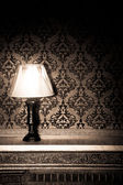 Vintage lamp on old fireplace in room with red rocco pattern — Stock fotografie