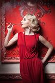 Sensuell kvinna röd klänning rökning i vintage rum — Stockfoto