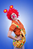 Happy woman clown on blue background — Stock Photo