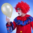 Happy clown with balloon on blue background — Stock Photo