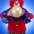 Clown with a ballon in hands on blue background — Stock Photo #48444779