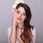 Beautiful brunette with flowers in head and red lipstick — Stock Photo