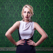 Woman in fashion pose on green vintage background — Stock Photo