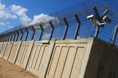 A secured industrial zone with concrete fence — Stock Photo